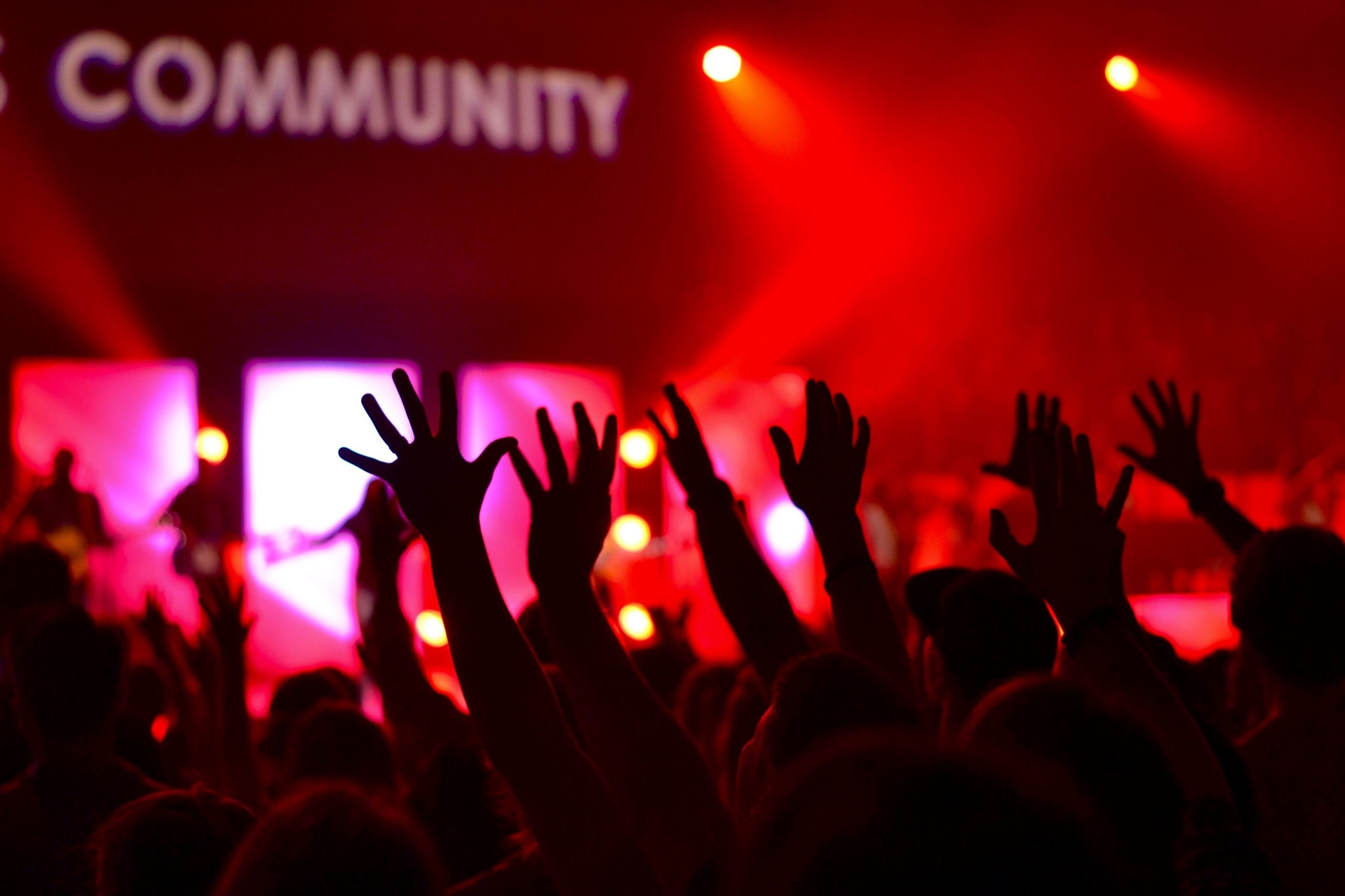 The image shows a nightclub environment with the word community above a bunch of raised hands.